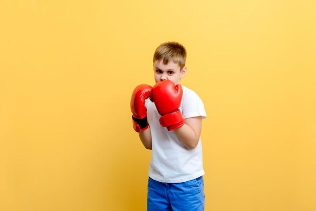 Dziecko w bokserskich rękawiczkach na ściennym tle