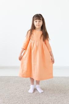 Dziecko w brzoskwiniowej sukience pozuje na białej ścianie