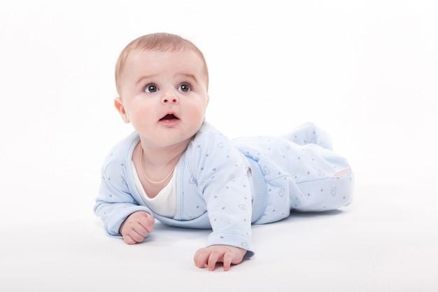 Dziecko w ciele leży na brzuchu na białym i