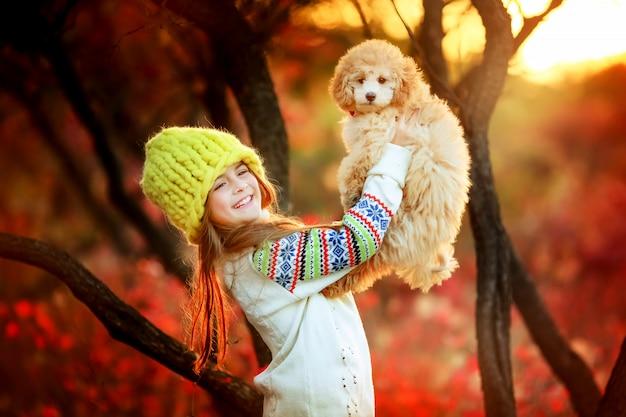 Dziecko w ciepłym kapeluszu z wełny jesienią w promieniach spadek chwytów na rękach psa domowego