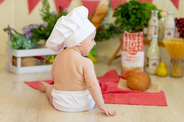 Dziecko w czapce kucharza siedzi z powrotem z mąką i warzywami
