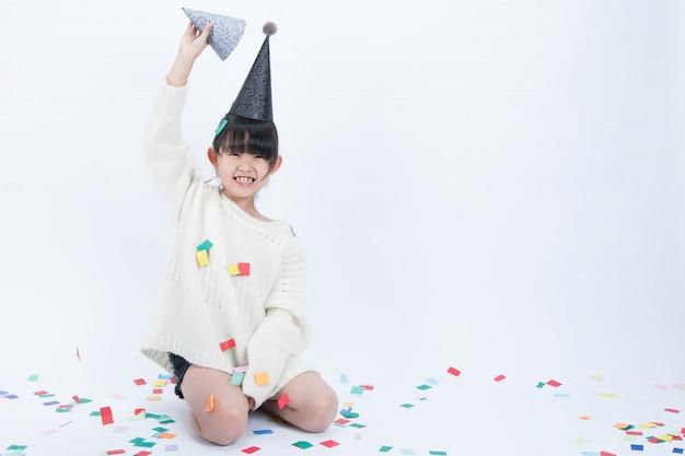 Dziecko w czarnym kapeluszu imprezowym dobrze się bawi. białe tło i czarny kapelusz pasują do siebie.
