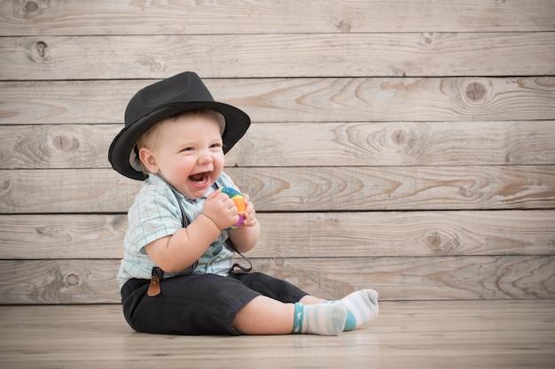 Dziecko w czarnym kapeluszu, koszuli i szortach spodenki na drewnie