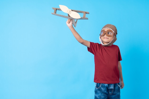 Dziecko w czerwonej koszuli marzy jak pilot trzymający papierowy samolot