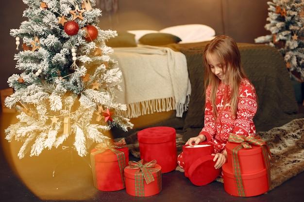 Dziecko w czerwonej piżamie. córka siedzi w pobliżu choinki.
