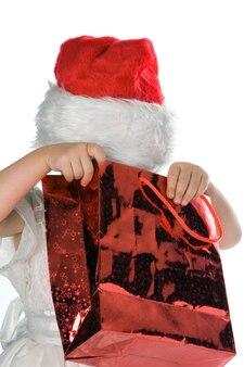 Dziecko w czerwonym kapeluszu świętego mikołaja patrzące na czerwony prezent na białym tle