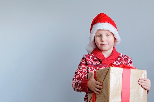 Dziecko w czerwonym kapeluszu, trzymając w ręku pudełko świąteczne. chłopiec na szarym tle. koncepcja nowego roku i świąt.