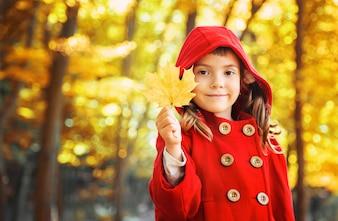 Dziecko w czerwonym płaszczu z jesiennych liści. Kocham jesień. Selektywna ostrość.