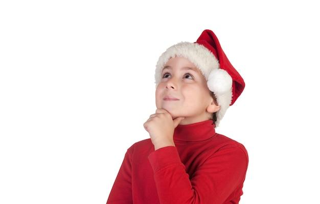 Dziecko w czerwonym świątecznym kapeluszu wyobrażające sobie coś na białym tle