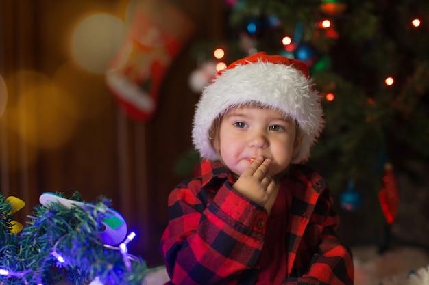 Dziecko w czerwonym ubraniu siedzi i czeka na nowy rok. koncepcja obchodzenia bożego narodzenia o północy. kostium świąteczny