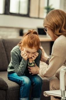 Dziecko w depresji. smutna rudowłosa dziewczyna trzymająca się za policzki w depresji