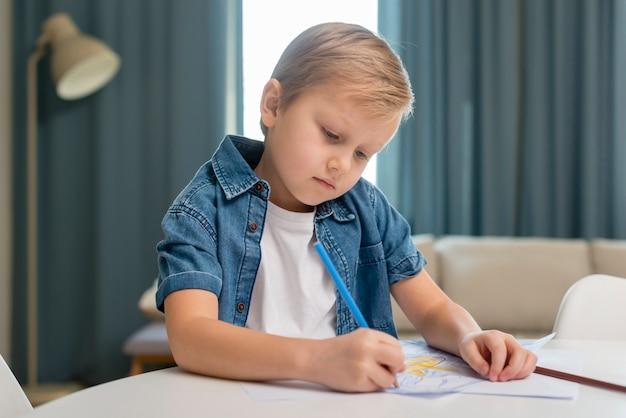 Dziecko w domu siedzi przy stole i pisze