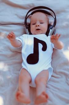 Dziecko w duże słuchawki leżąc na łóżku