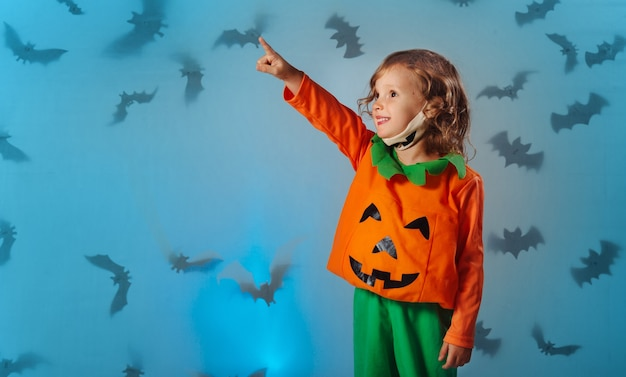 Dziecko w dyniowym kostiumie karnawałowym i masce medycznej wskazuje ręką na nietoperze w halloween