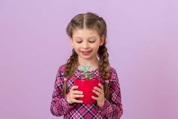 Dziecko w fioletowej sukience w kratkę trzyma zieloną roślinę w czerwonej doniczce.
