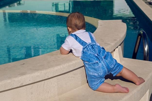 Dziecko w garniturze siedzi na brzegu basenu