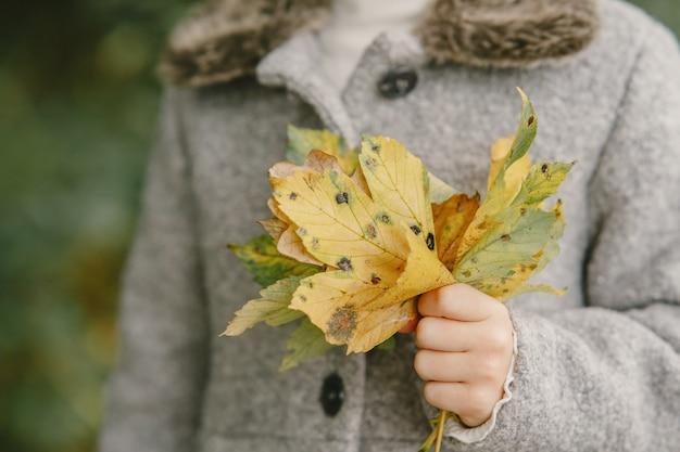 Dziecko w jesiennym parku. dziecko w szarym płaszczu.