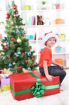 Dziecko w kapeluszu santa w pobliżu choinki z dużym prezentem