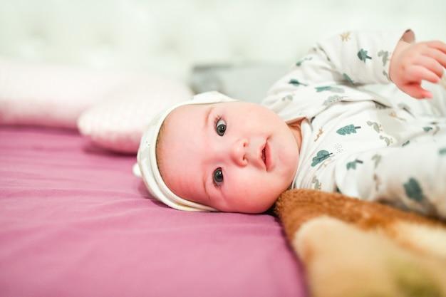 Dziecko w kapeluszu w domu. słodkie dziecko w kapeluszu na łóżku, zabawy.