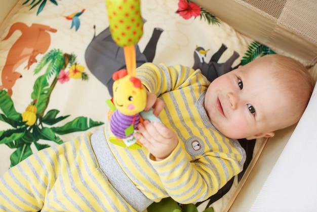 Dziecko w kojec i bawić się zabawkami
