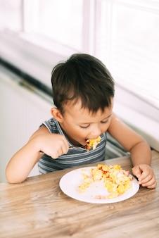 Dziecko w koszulce w kuchni je widelcem omlet z kiełbasą i pomidorami