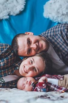 Dziecko w kraciastą koszulę z tatą i mamą. dziecko i jego rodzice. rodzinne zdjęcie. opierajcie się na policzkach