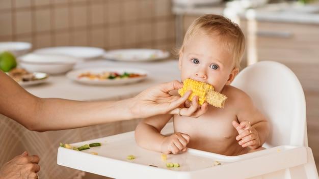 Dziecko w krzesełku do jedzenia kukurydzy