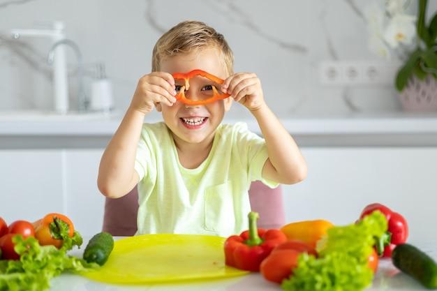 Dziecko w kuchni w domu je warzywa dziecko uśmiechnięte zdrowe jedzenie koncepcja wegetariańska