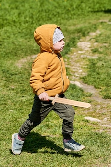 Dziecko w kurtce i kapeluszu z drewnianym mieczem w rękach bawi się na ulicy. chłopiec z zabawkowym mieczem chodzi