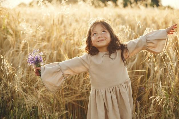 Dziecko w letnim polu. mała dziewczynka w ślicznej brązowej sukience.