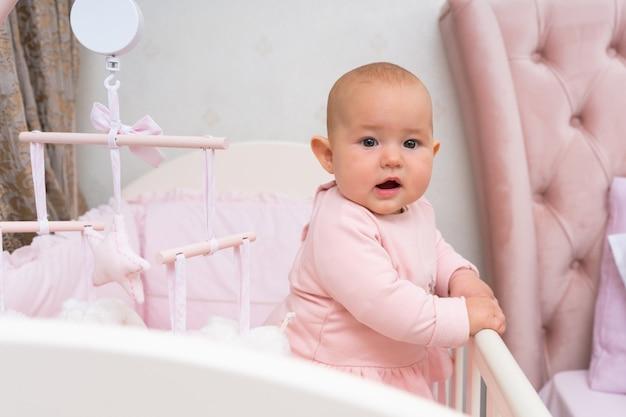 Dziecko w łóżeczku i różowej sypialni z wiszącą karuzelą.