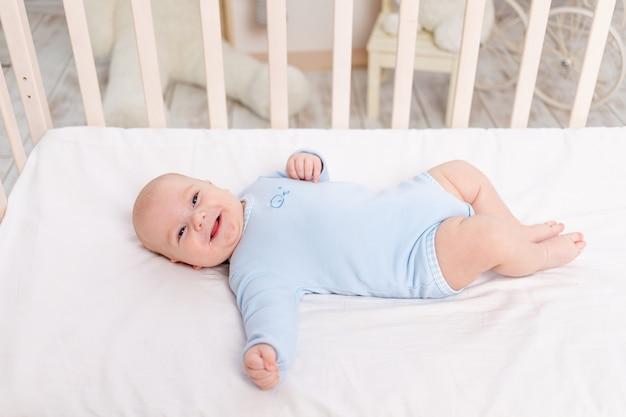 Dziecko w łóżeczku, śliczny sześciomiesięczny chłopiec leżący w przedszkolu na łóżku
