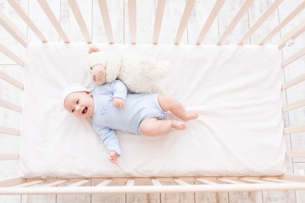 Dziecko w łóżeczku z pluszową zabawką idzie spać lub obudziło się rano, koncepcja rodziny i porodu