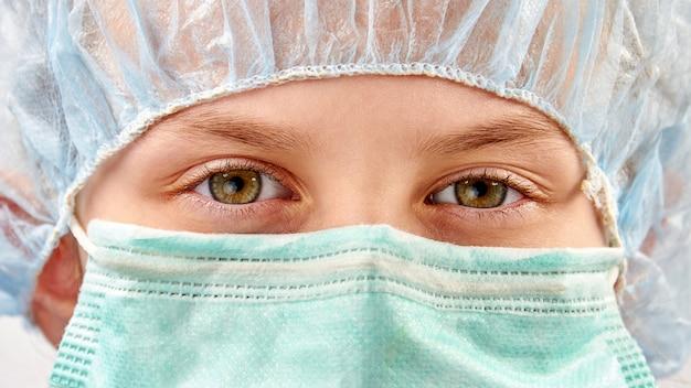 Dziecko w masce medycznej i czapce ochronnej. ochrona przed koronawirusem. zbliżenie