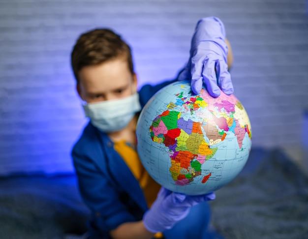Dziecko w masce medycznej trzyma kulę ziemską. mały chłopiec leczy planetę. pojęcie zanieczyszczenia powietrza i środowiska.