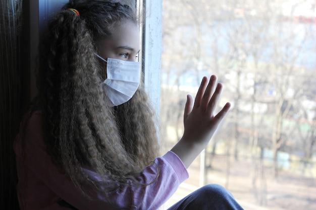 Dziecko w masce na twarzy siedzi na parapecie. zostań w domu.