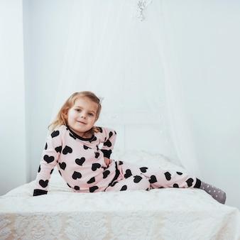 Dziecko w miękkiej ciepłej piżamie, grając w łóżku
