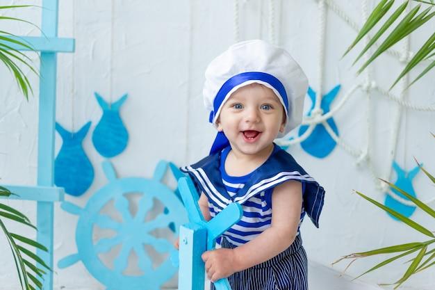 Dziecko w morskiej strefie ze statkiem w marynarskiej kamizelce, koncepcja lata i podróży