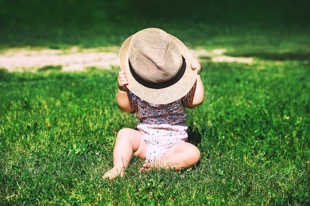 Dziecko w naturze najsłodsza dziewczynka w zielonej trawie bawi się słomianym kapeluszem w okresie letnim