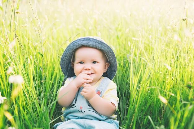 Dziecko w naturze najsłodsza uśmiechnięta dziewczynka w zielonej trawie z kwiatami w okresie letnim