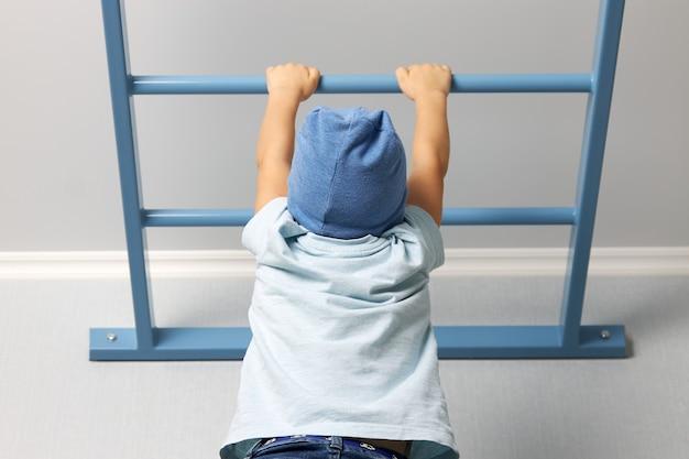 Dziecko w niebieskiej koszulce i kapeluszu wspina się po drabinie pod sufitem. domowe zajęcia sportowe