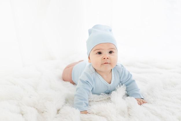 Dziecko w niebieskim ubraniu leży na brzuchu na białym dywanie