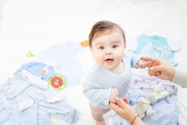 Dziecko w niebieskim ubranku siedzi wśród dziecięcych akcesoriów i ubrań, trzymając się za ręce z matką