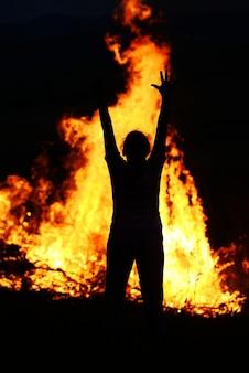 Dziecko w ogniu z szeroko otwartymi ramionami