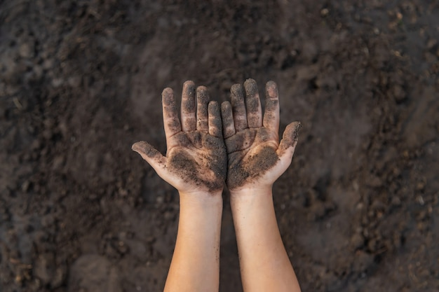 Dziecko w ogrodzie z ziemią w dłoniach.