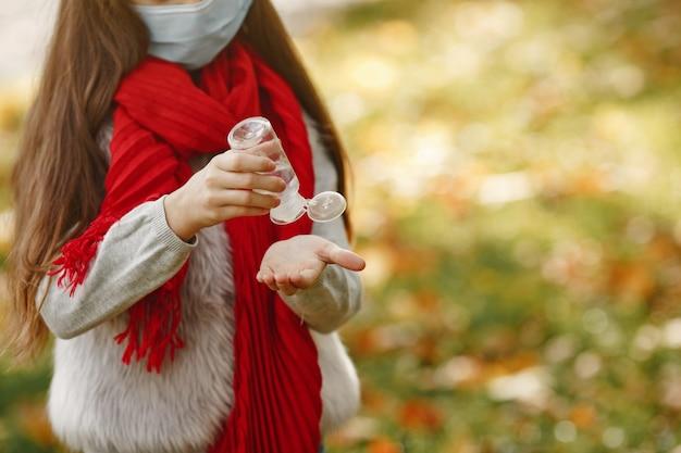 Dziecko w parku jesienią. motyw koronawirusa. dziewczyna w czerwonym szaliku. dzieci używają środka antyseptycznego.