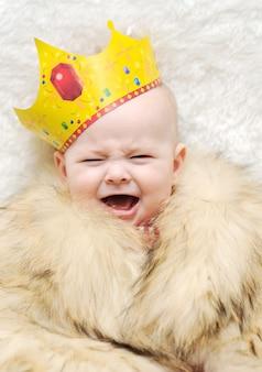 Dziecko w pelerynie futra i korony na białym tle. dziecko płacze