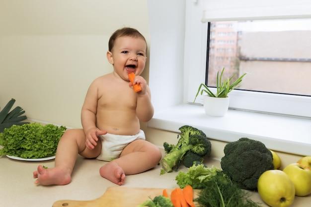Dziecko w pieluszce siedzi na kuchennym stole. dziecko bawi się i bawi ze świeżymi organicznymi warzywami i owocami.