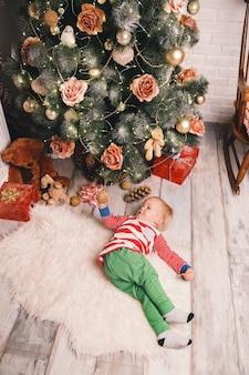Dziecko w piżamie spędza czas z rodziną we wnętrzu domu na tle choinki