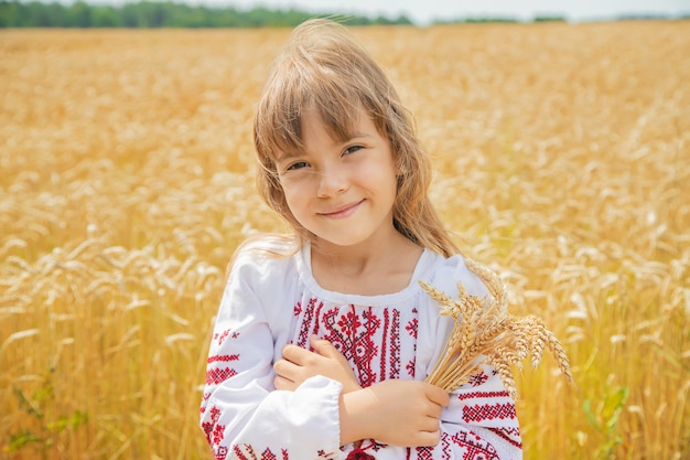 Dziecko w polu pszenicy w haftowanej koszuli.